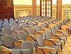 Stuhlreihenausschnitt in einem Hörsaal mit Mosaikwänden