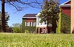 Student auf dem Rasen vor einem Wohnheim