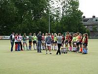 Eine Gruppe junger Feldhockey-Stipendiaten hören dem Trainer zu