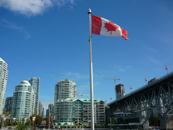 Kanadische Flagge vor Wolkenkratzern in Vancouver