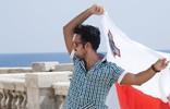 Student mit maltesischer Flagge am Meer