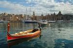 Luzzu im Mittelmeer vor einem maltesischen Hafen