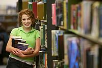 Studentin lehnt sich in Bibliothek an ein Bücherregal