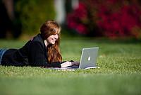 Studentin liest ein Buch auf dem Campusrasen
